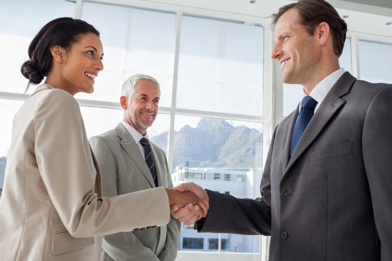 smiling-business-people-shaking-hands-smiling-colleague-beh-them-background-31098953